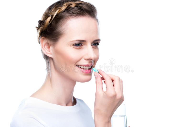 Woman with blue pill. Attractive woman with water and blue pill, isolated on white royalty free stock image