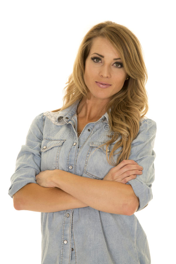 Woman in a blue shirt arms folded looking. A woman in her denim top with a serious expression on her face stock photography