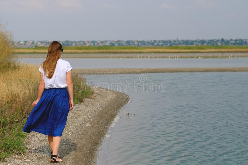 A woman in a blue skirt walking along the river royalty free stock photography