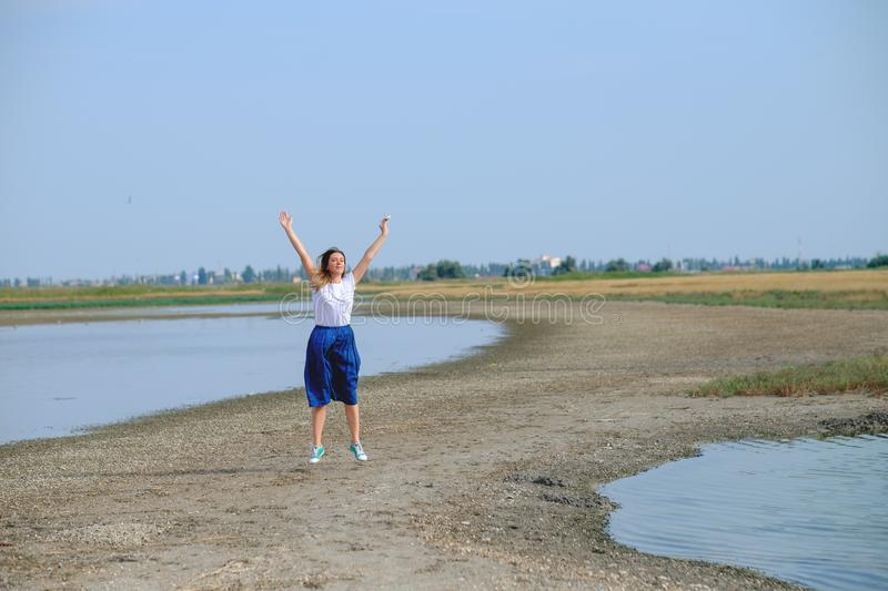 A woman in a blue skirt walking along the river stock images