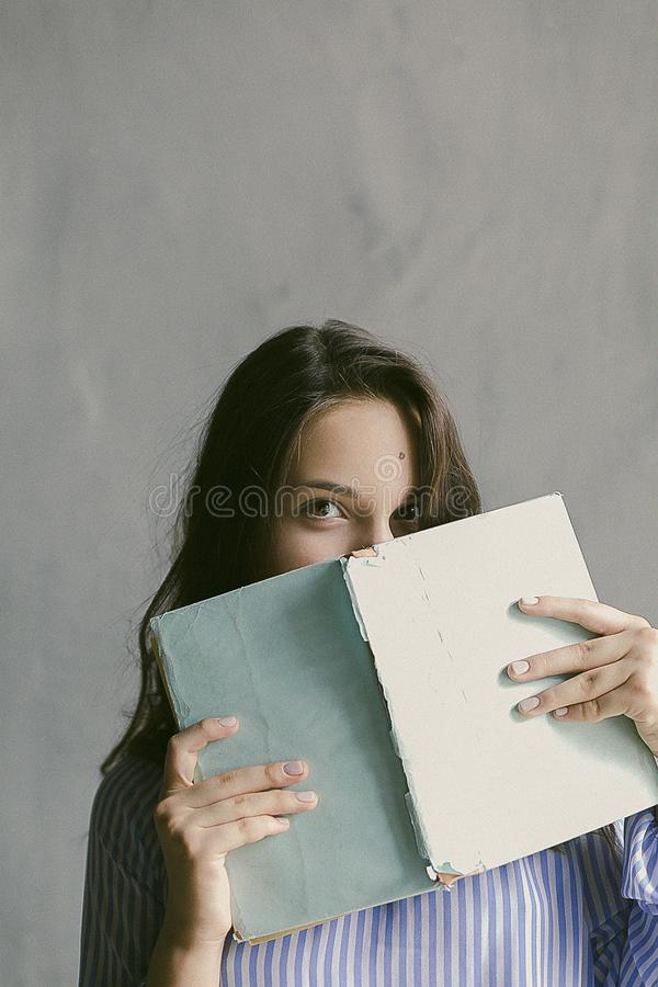 Woman in Blue Striped Flannel Shirt Holding a Book Indoors stock images