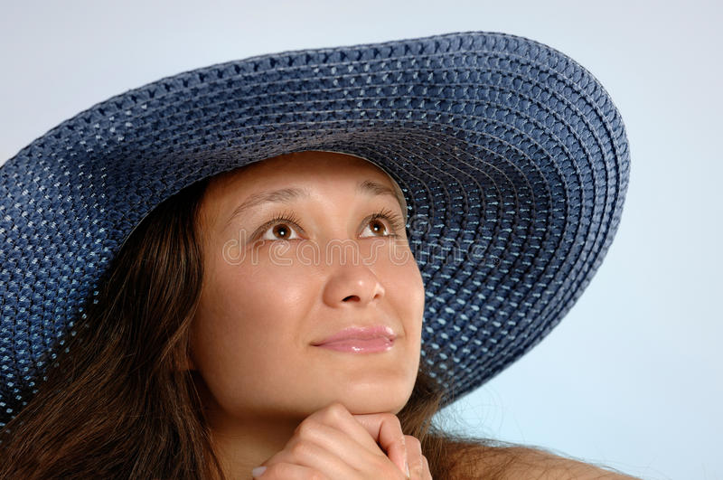 Woman in a Blue Sunhat. Portrait of a young woman in a blue sunhat with daydreaming romantic expression royalty free stock photography