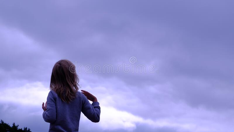 Woman in Blue Sweater Facing in Blue Clear Sky stock image