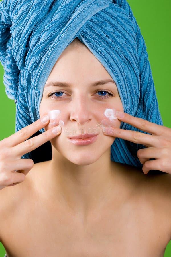 Woman In Blue Towel Applying Facial Cream Stock Photos