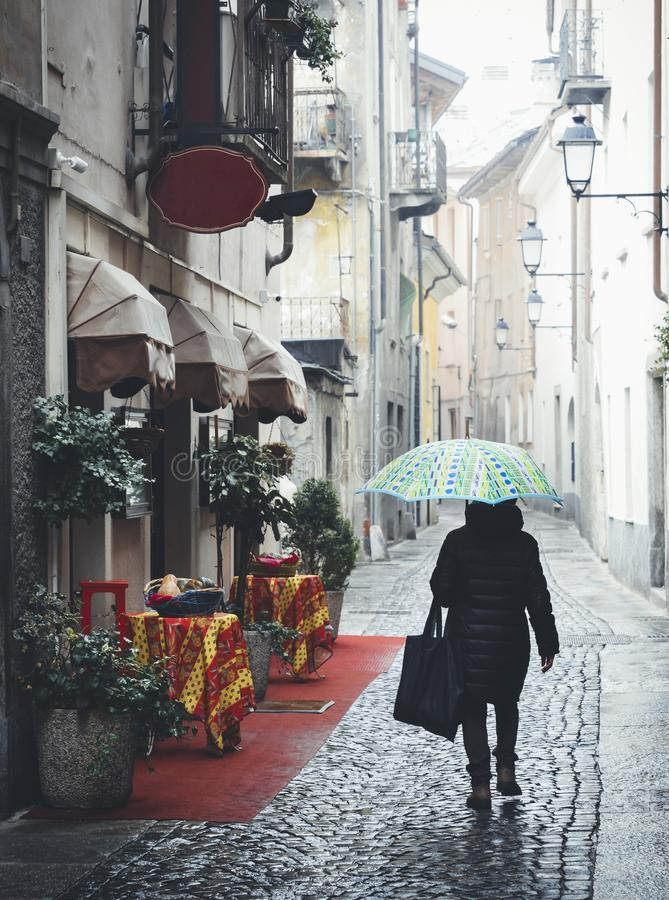 Woman with blue umbrella walks on quaint cobblestone alleyway in Aosta, Italy with inviting red carpet entrance to Italian restaur. Ant on left royalty free stock photo