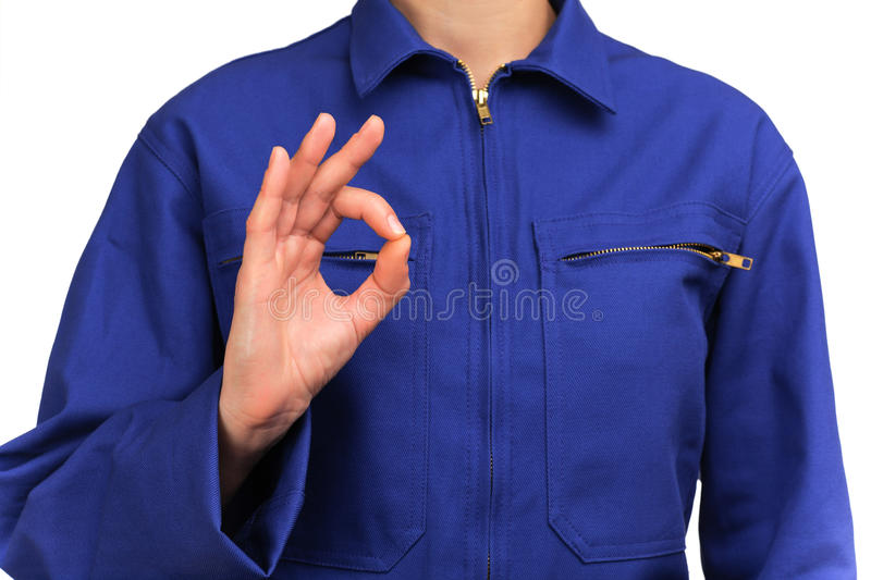Woman in blue work uniform making the sign all is well. Photograph of a bust of a woman in blue work uniform making the sign all is well royalty free stock photography