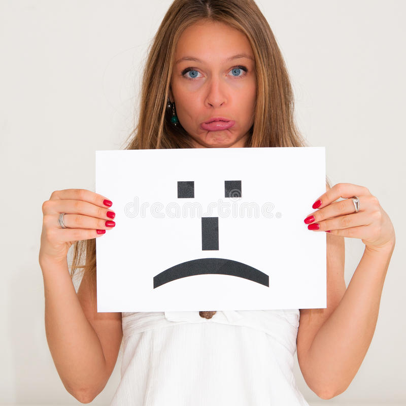 Woman with board sad emoticon face sign. Portrait young woman with board sad emoticon face sign royalty free stock images