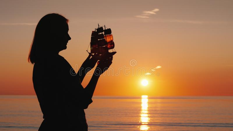 A woman with a boat in her hands stands by the sea, where the sun sets. Creativity and inspiration concept. royalty free stock photo