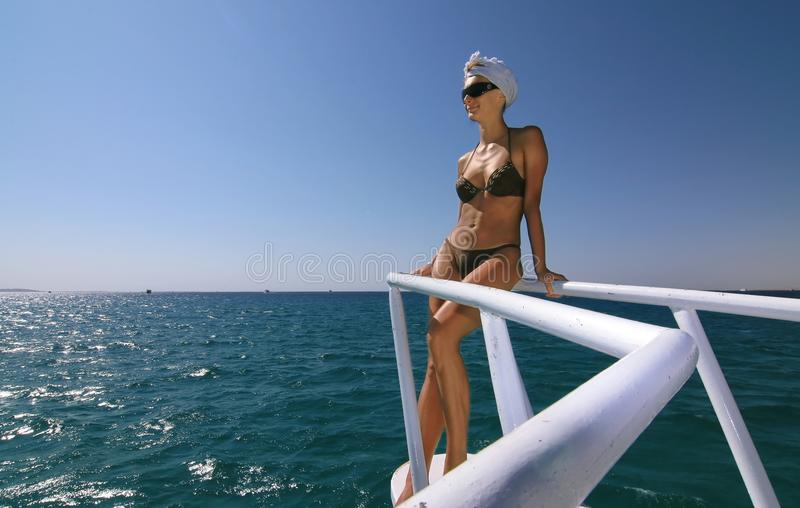 Woman on a boat, over the sea. Woman standing on a boat, looking far away stock image