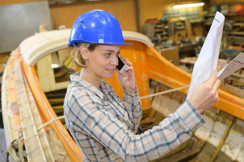 Woman in boatyard on telephone while looking at paperwork royalty free stock images