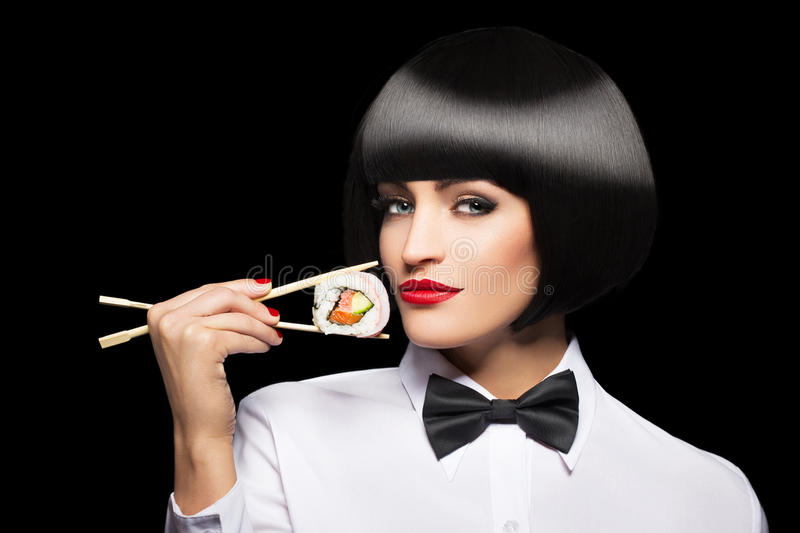Woman with bob cut hair holding sushi with chopsticks. Isolated on black stock photography