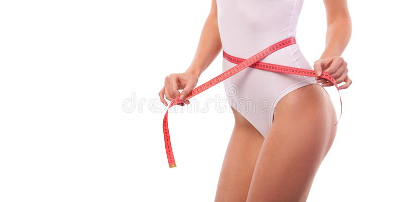 Woman body with measure tape. Close up of sporty and beautiful female body. Tanned woman measuring waist and hips with measuring royalty free stock photo