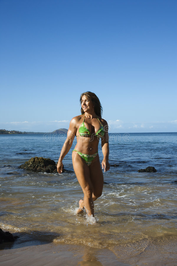 Woman bodybuilder at beach. royalty free stock image