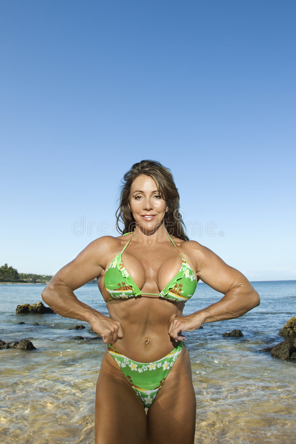 Woman bodybuilder at beach. royalty free stock images