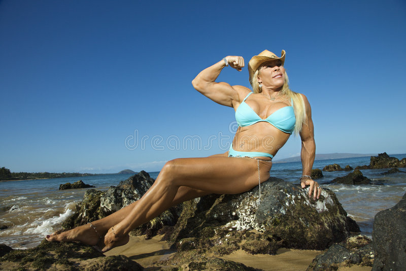 Woman bodybuilder at beach. royalty free stock photography