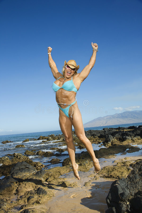 Woman bodybuilder jumping. royalty free stock images