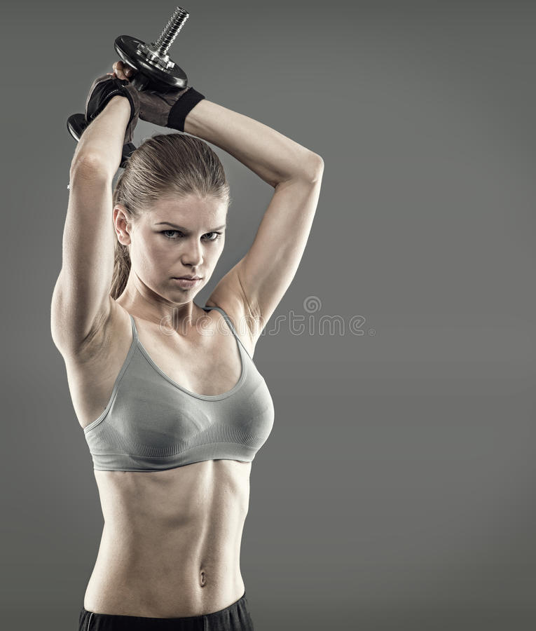 Woman bodybuilder. Young athletic sporty woman bodybuilder lifting dumbbell. Energetic strong muscular build female pumping hands stock photo