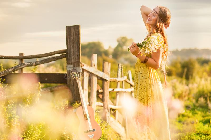 woman bohemian style, holding a flowers on field at light of sunset stock photo