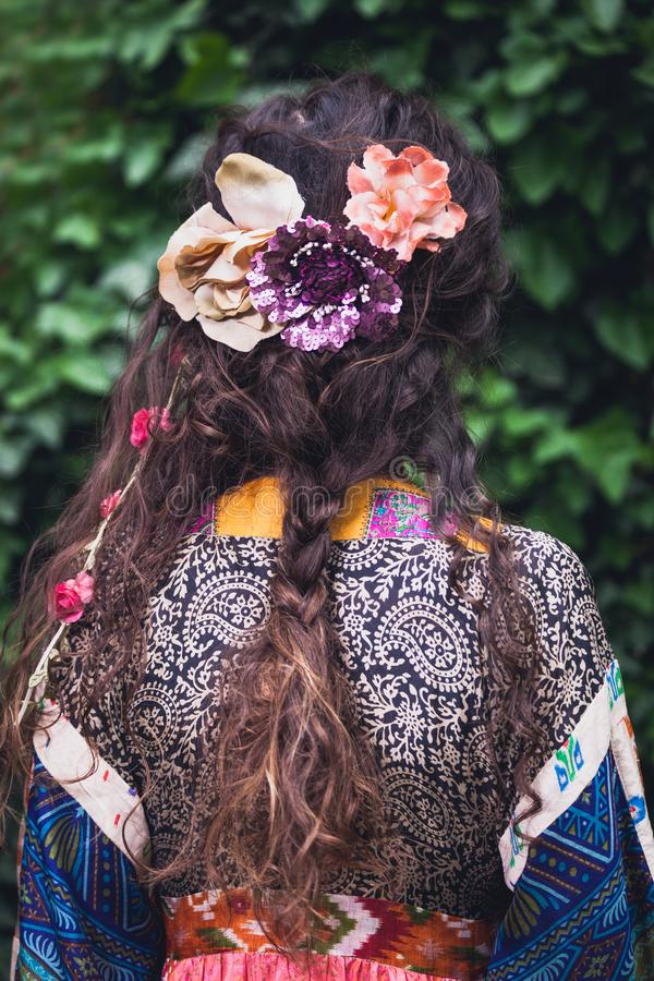 Woman with boho style hair loose braid and decorative flowers fashion accessories outdoor summer day back royalty free stock photos