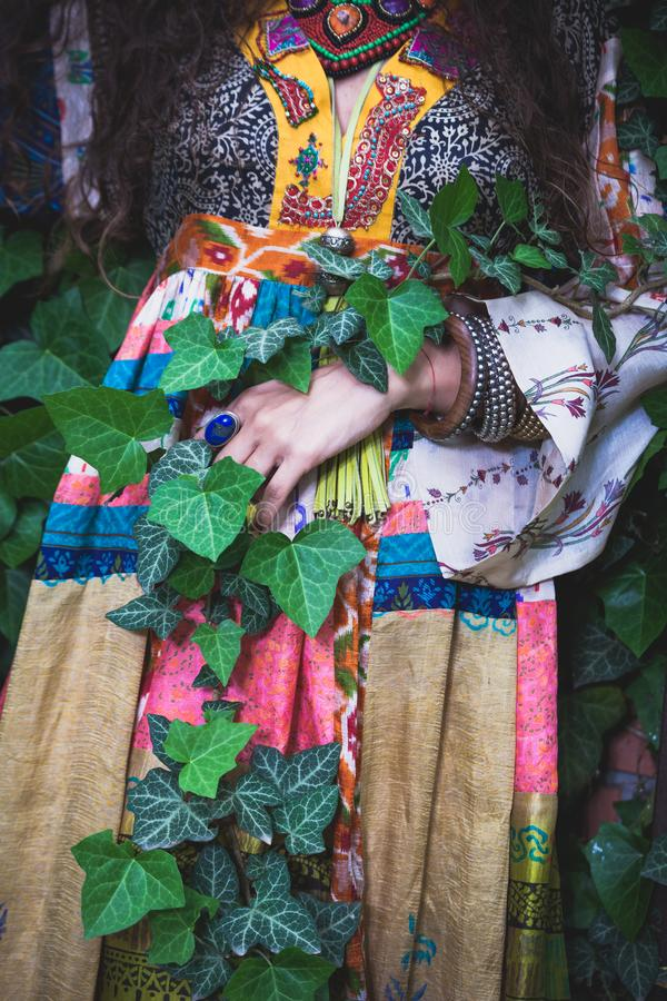 Woman in boho style silk dress in garden wrapped in green ivy lower body summer royalty free stock image