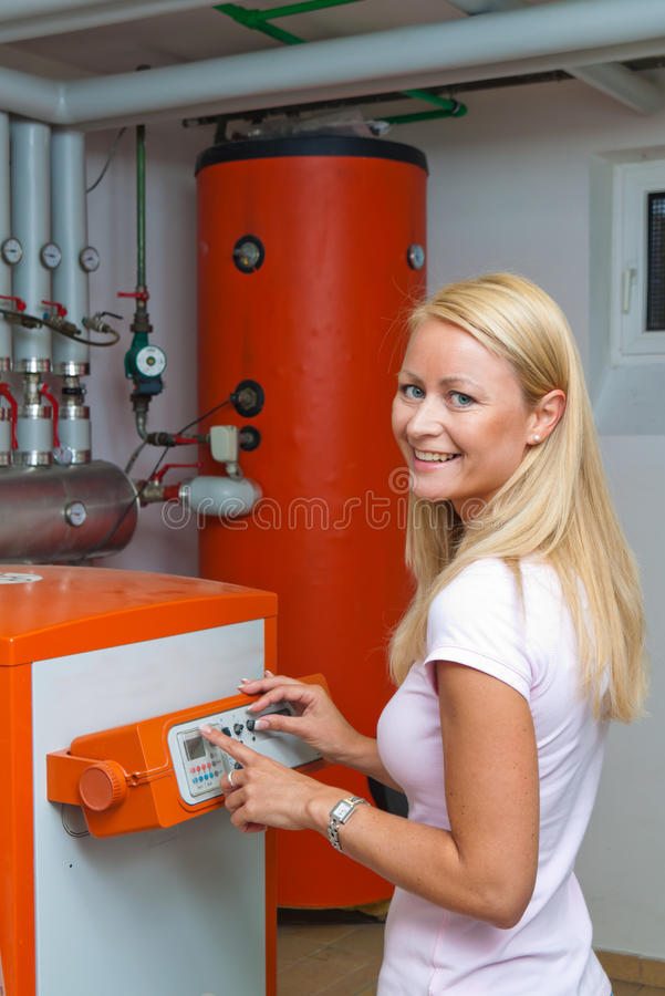 Woman in the boiler. A young woman in the boiler room for heating. Save energy royalty free stock images