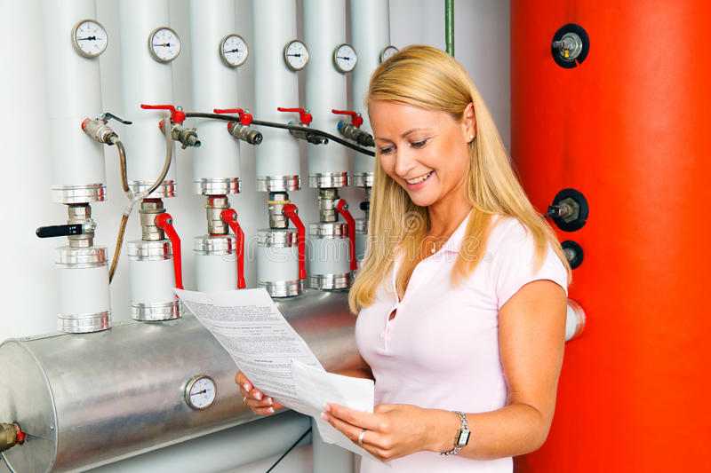 Woman in the boiler room for heating. A young woman in the boiler room for heating. Save energy royalty free stock image
