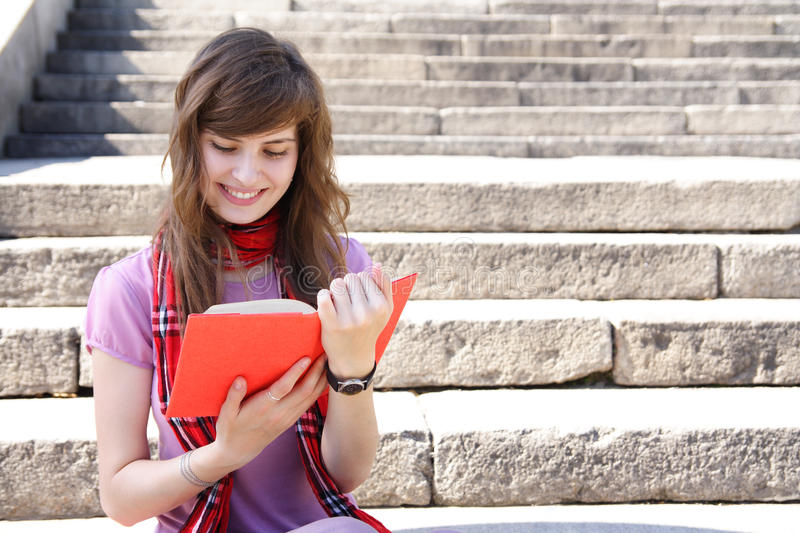 Woman with book. Young beautiful woman reads the book outdoors royalty free stock photography