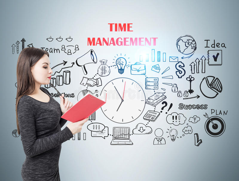 Woman with book and time management. Portrait of a young businesswoman wearing a dress and reading a red book near a gray wall with a time mangement sketch stock photos