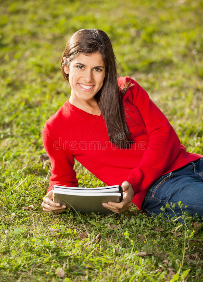 Woman With Books Relaxing On Grass At College Stock Image