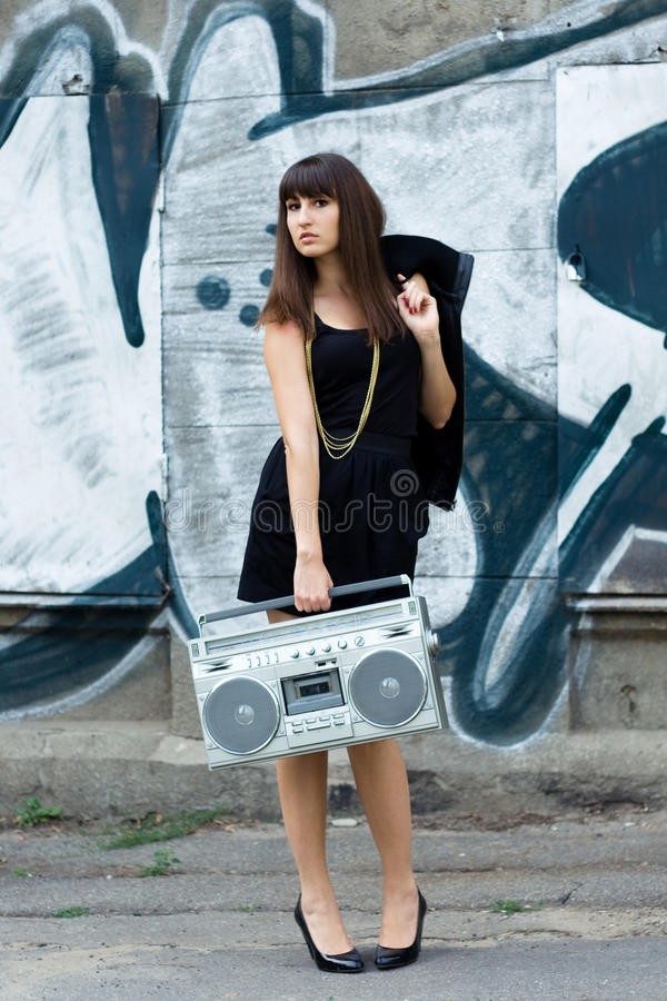 Woman with boom box on the street. Beautiful woman with boom box on the street and graffiti wall royalty free stock photography