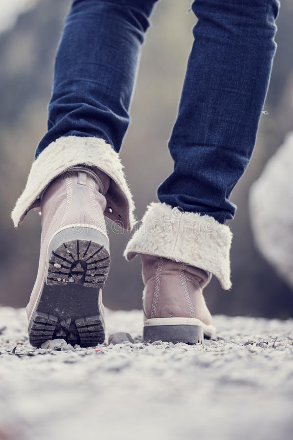 Woman in boots hiking along a rural path stock images