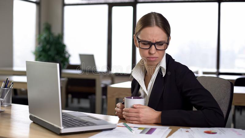 Woman bored working at computer, exhausted and unmotivated, coffee break royalty free stock photo