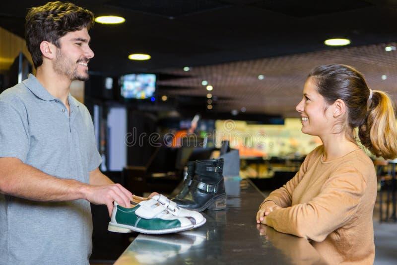 Woman borrowing pair bowling shoes stock photos