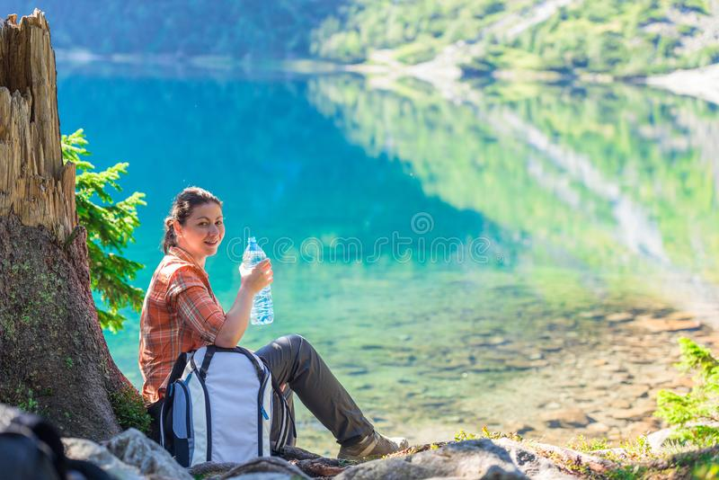 woman with a bottle of drinking water rests near a beautiful scenic lake in the mountains royalty free stock images