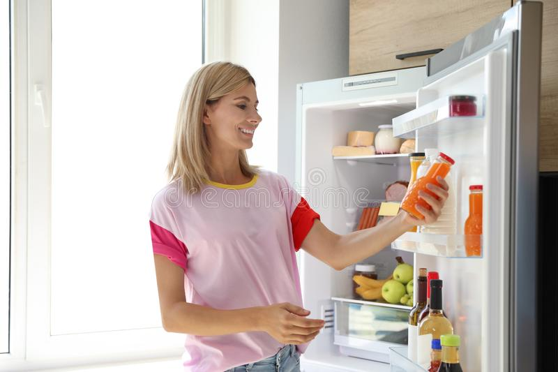 Woman with bottle of juice near open refrigerator in. Kitchen royalty free stock photos