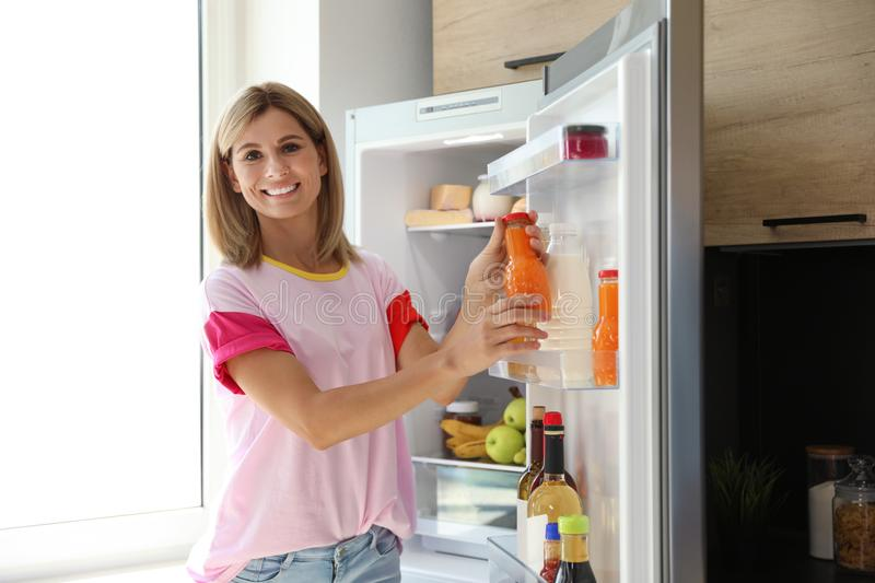 Woman with bottle of juice near open refrigerator. In kitchen royalty free stock image