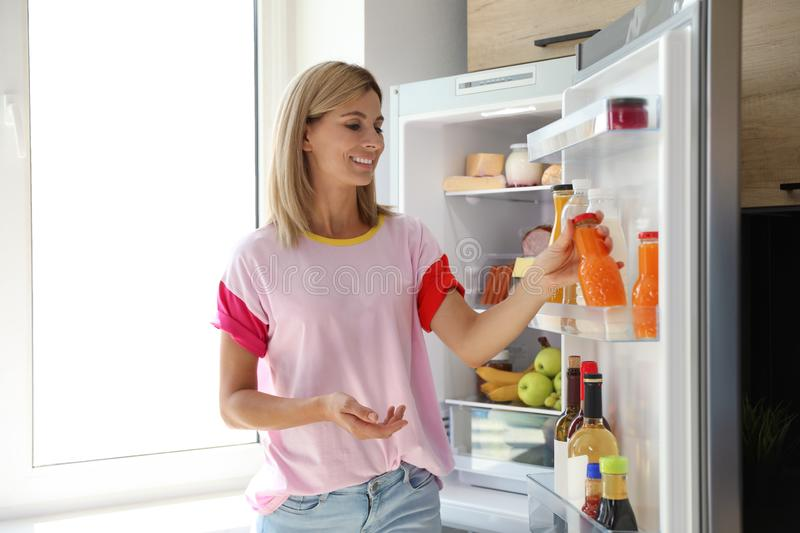 Woman with bottle of juice near open refrigerator royalty free stock photography