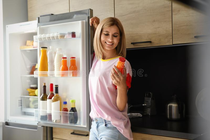Woman with bottle of juice near refrigerator. In kitchen royalty free stock image