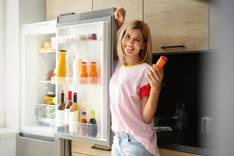 Woman with bottle of juice  refrigerator in kitchen. Woman with bottle of juice near refrigerator in kitchen stock image