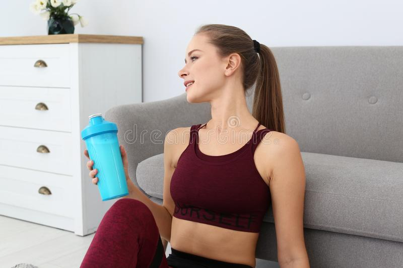 Woman with bottle of protein shake near sofa royalty free stock image