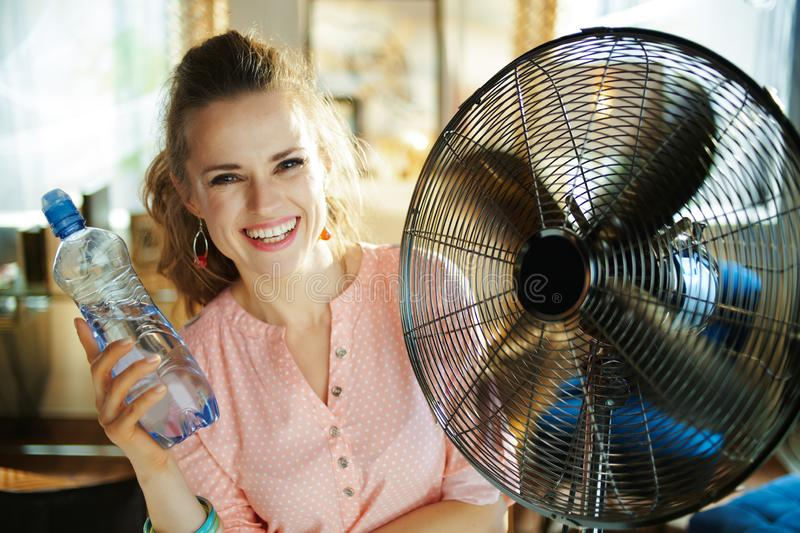 Woman with bottle of water enjoying fresh air in front of fan. Happy modern woman in the modern living room in sunny hot summer day showing cold bottle of water stock photography