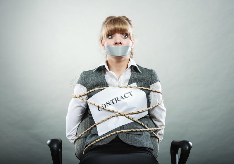 Woman bound by contract terms with taped mouth. Afraid businesswoman bound by contract terms and conditions with mouth taped shut. Scared woman tied to chair royalty free stock photography