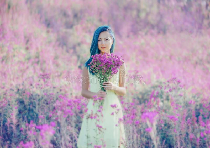 Woman with bouquet of purple flowers. royalty free stock photography