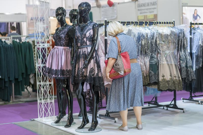 Woman in a boutique chooses clothes. women shopping in fashion mall, choosing new clothes stock photography