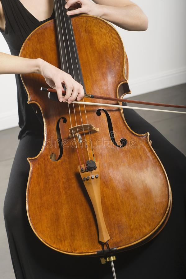 Woman Bowing A Cello. Midsection of woman bowing a cello stock image