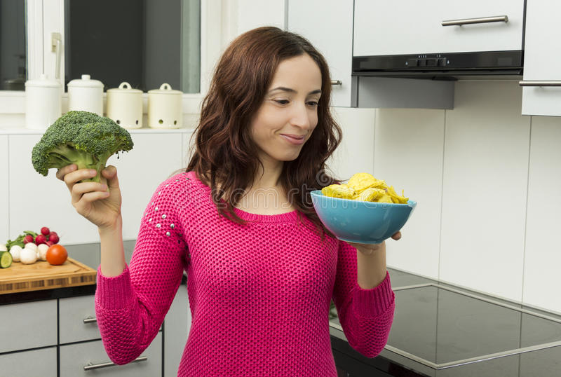 Woman with a bowl of potato chips and broccoli stock photography