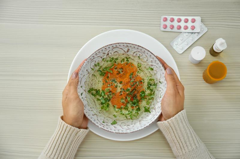Woman with bowl of soup at wooden table. Flu treatment. Woman with bowl of soup at wooden table, top view. Flu treatment stock photography