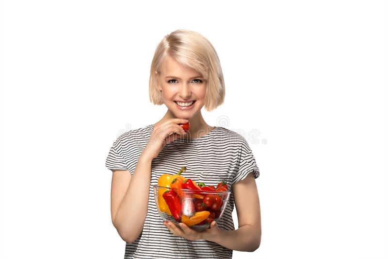 Woman with bowl of vegetables. Young woman holding bowl of vegetables pepper and tomatoes isolated on white background stock photo