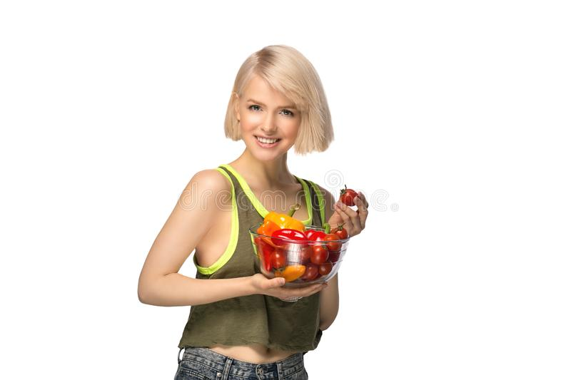 Woman with bowl of vegetables. Young woman holding bowl of vegetables pepper and tomatoes isolated on white background stock photos