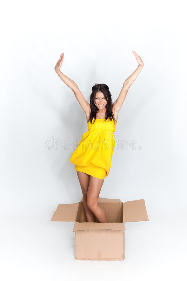 Woman in box. A woman popping out of a cardboard box stock photo